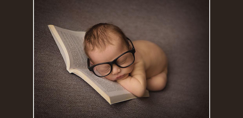 Newborn Baby reading a book.